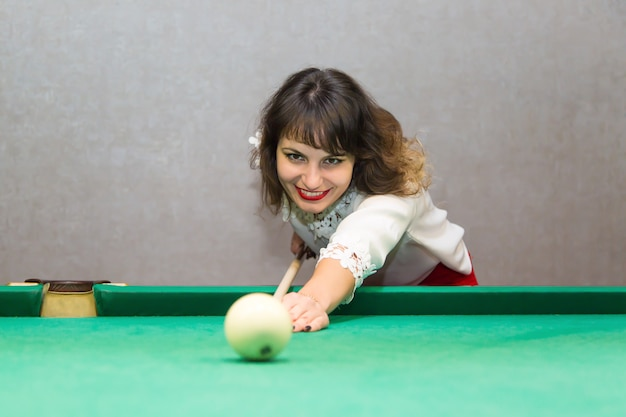Femme brune joue au billard