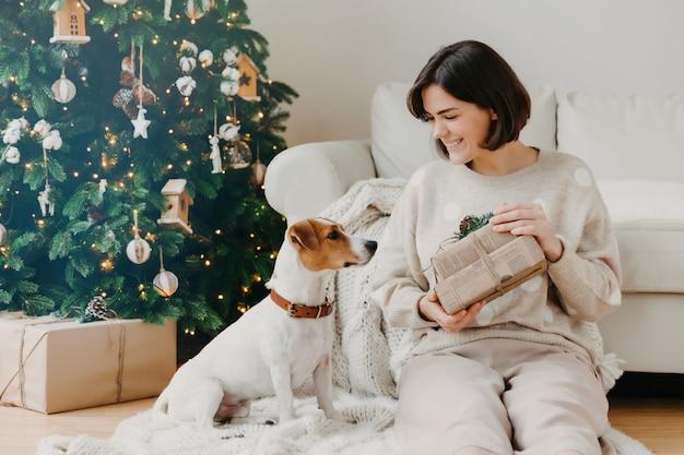 Femme brune joyeuse montre des cadeaux reçus à son chien préféré, pose ensemble sur le sol dans une chambre confortable, a une ambiance festive, prépare noël