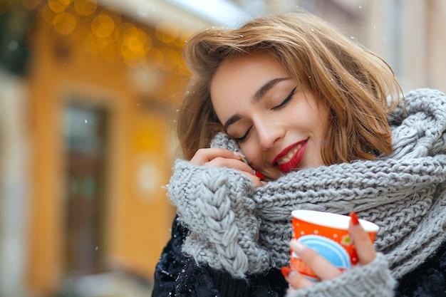Une femme brune joyeuse porte une écharpe en tricot et profite du temps neigeux et boit du café. espace libre