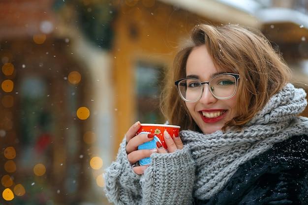 Une femme brune joyeuse porte une écharpe tricotée et des lunettes boit du café dans la rue pendant les chutes de neige. espace libre