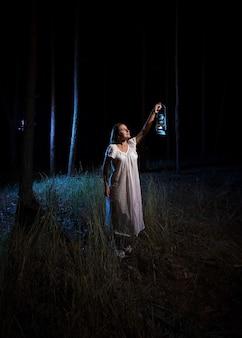 Femme brune avec une lanterne à gaz éclairant la forêt la nuit