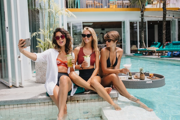 Femme brune ludique à lunettes de soleil faisant selfie avec des amis à la station. des femmes caucasiennes bronzées prenant une photo d'eux-mêmes dans la piscine.