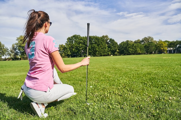 Femme brune à lunettes de soleil vérifiant le sol sur le practice