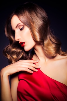 Femme brune de luxe en robe rouge à la peau claire et au maquillage sombre du soir: oeil de chat vert et fards à paupières bruns. coiffure ondulée. fond sombre