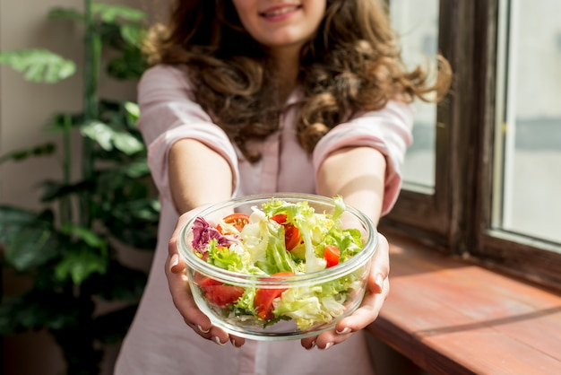 Femme brune mangeant une salade