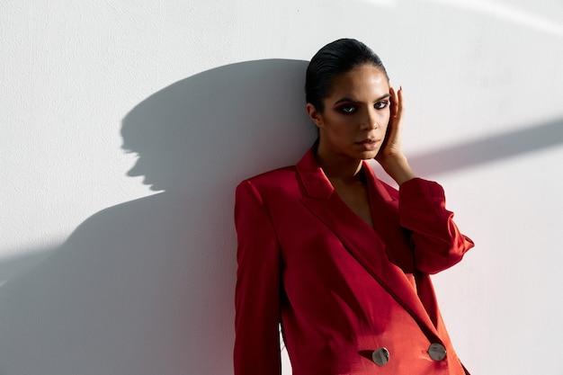 Femme brune avec un maquillage lumineux et dans une veste rouge appuyée contre le mur à l'intérieur de l'espace de copie.