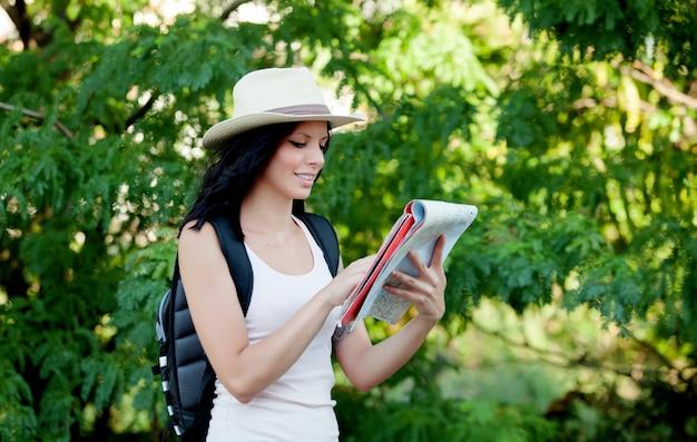 Femme brune marchant dans les bois tout en se référant à une carte