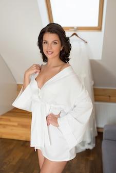 Femme brune mariée en robe de soie blanche se préparant au mariage sur fond de robe de mariée blanche