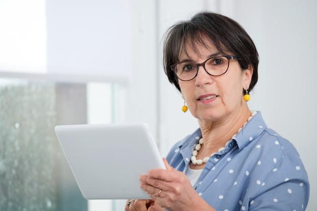 Femme brune mature assise sur un canapé à l'aide d'une tablette numérique