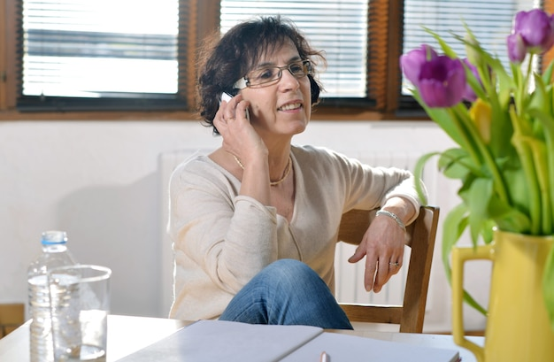 Femme brune mature détendue au bureau avec un smartphone