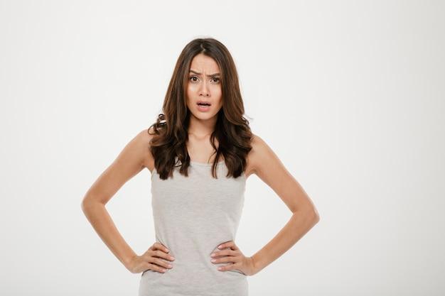 Femme brune mécontente avec les bras sur les hanches en regardant la caméra sur gris