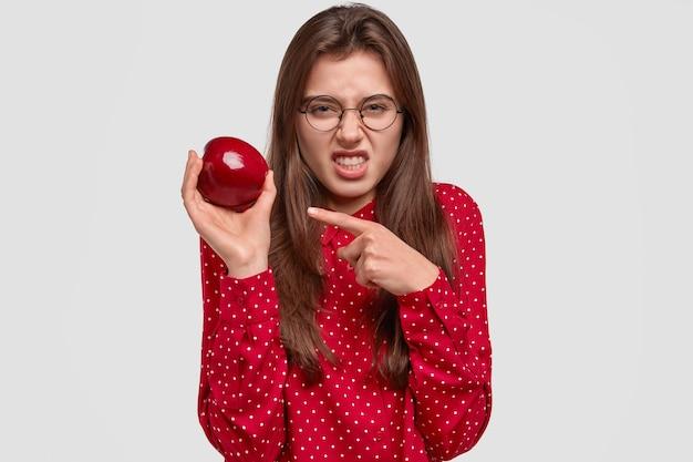 Une femme brune mécontente serre les dents, fronce les sourcils de mécontentement, tient la pomme, n'aime pas son goût