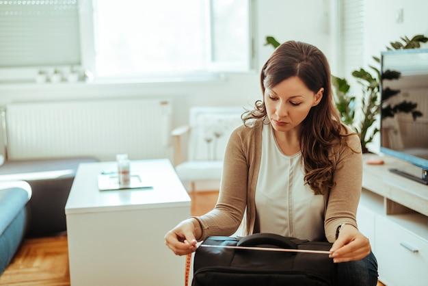 Femme brune mesurant ses bagages avant de partir en vacances.