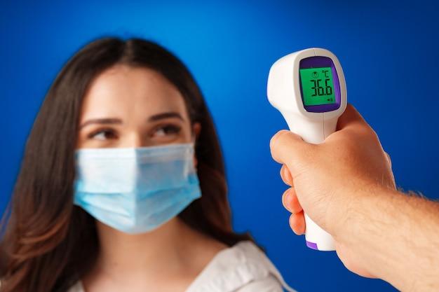 Femme brune obtenant un contrôle de la température avec un thermomètre infrarouge sur fond bleu