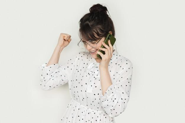 Femme brune parlant au téléphone et faisant des gestes le signe oui sur un mur blanc