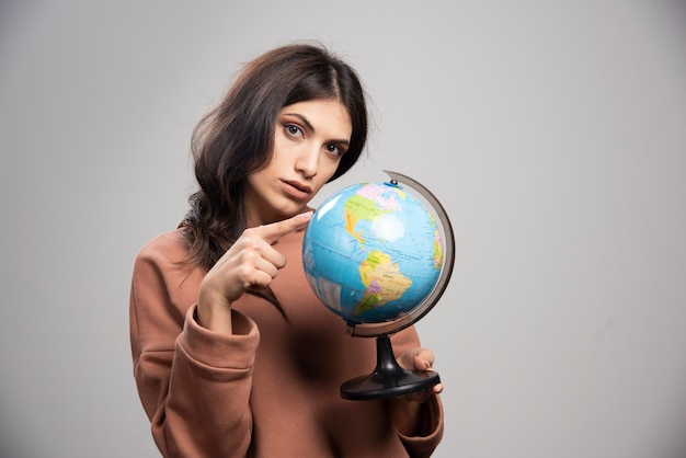 Femme brune pointant sur globe sur fond gris