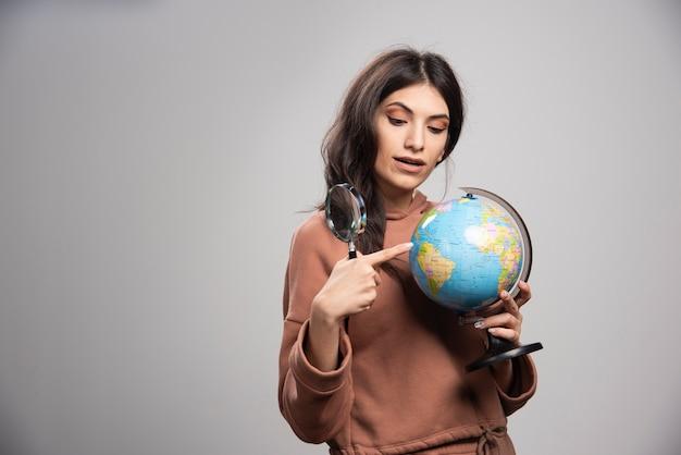 Femme brune pointant sur une petite place sur le globe