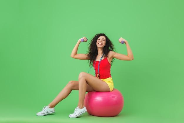 Femme brune portant des vêtements d'été soulevant des haltères alors qu'elle était assise sur un ballon de fitness pendant l'aérobic contre le mur vert