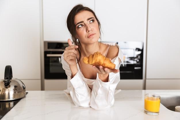 Femme brune portant des vêtements en soie manger un croissant, pendant le petit-déjeuner dans la cuisine à la maison