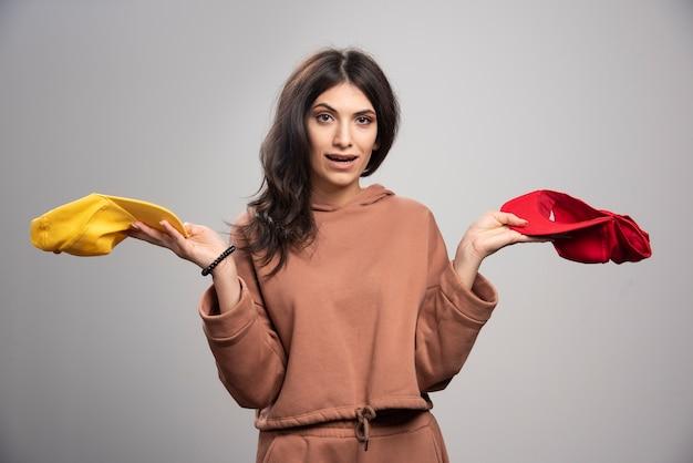 Femme brune posant avec des casquettes colorées