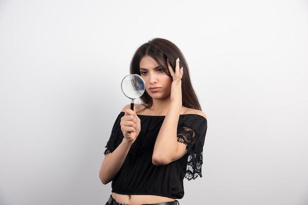 Femme brune posant avec une loupe.
