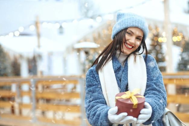 Femme brune positive en manteau d'hiver tenant une boîte-cadeau à la foire de noël pendant les chutes de neige. espace pour le texte