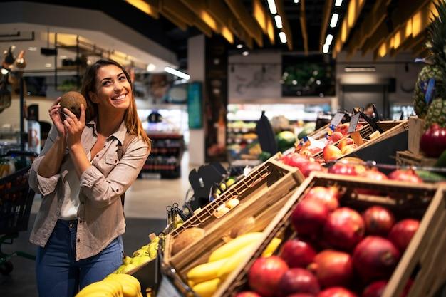 Femme brune positive tenant la noix de coco au département des fruits de l'épicerie
