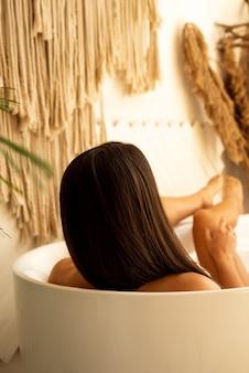 Femme brune prenant un bain et toucher sa jambe. elle est assise dans la salle de bain