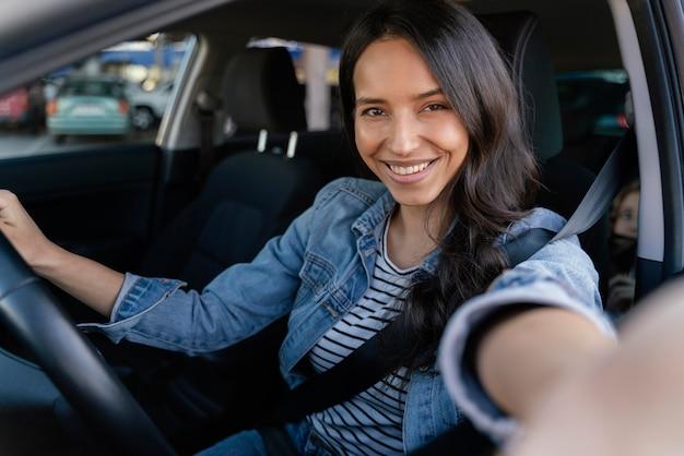 Femme brune prenant un selfie dans sa voiture