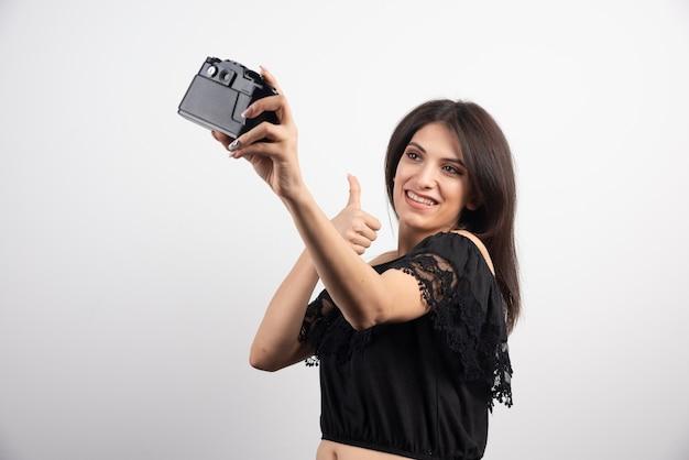 Femme brune prenant des selfies avec caméra