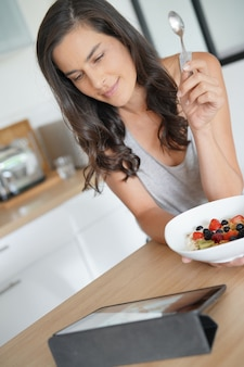 Femme brune prenant son petit déjeuner sain à la maison