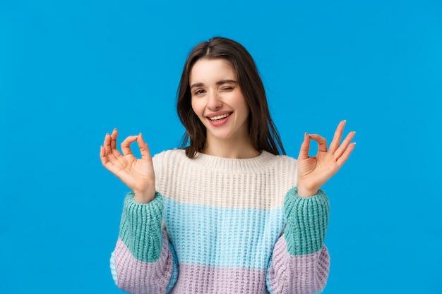Femme brune avec un pull d'hiver faisant signe ok
