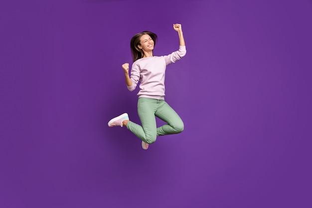 Femme brune en pull pastel posant contre le mur violet