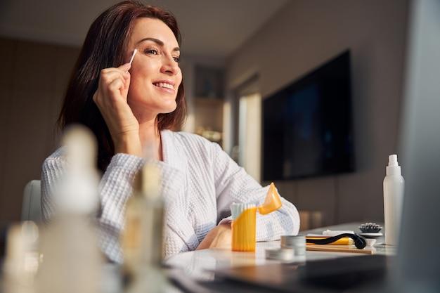 Femme brune ravie positive faisant le maquillage quotidien