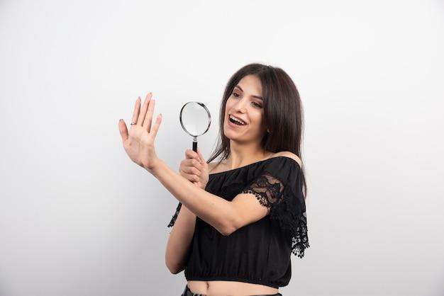 Femme brune regardant sa main avec une loupe.