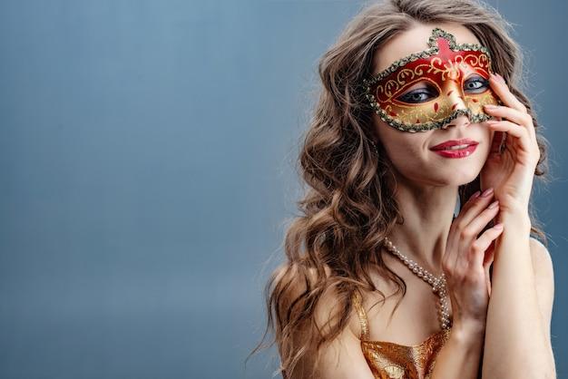 Femme brune rêveuse dans un masque de carnaval coloré sur fond bleu