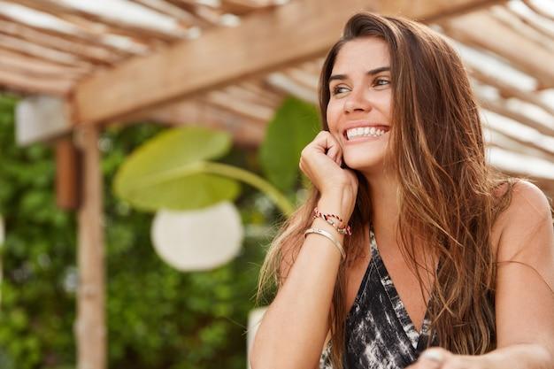 Une femme brune rêveuse avec une expression joyeuse recrée pendant les vacances d'été dans un pays tropical, heureuse d'admirer une vue magnifique et a une conversation agréable avec un beau mec étranger. temps de repos