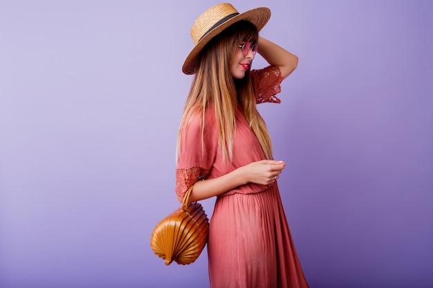 Femme brune en robe rose tendance et chapeau de paille tenant un sac en bambou sur violet.