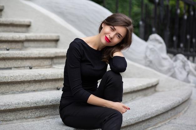 Une femme brune romantique aux lèvres rouges porte un costume noir assis sur les escaliers en béton blanc