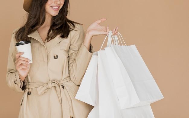 Femme brune avec des sacs à provisions et café