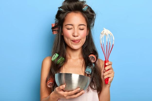 Une femme brune satisfaite fouette la crème sure dans un bol, porte des bigoudis