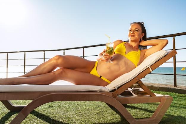 Femme brune se détendre sur un transat dans un club de plage