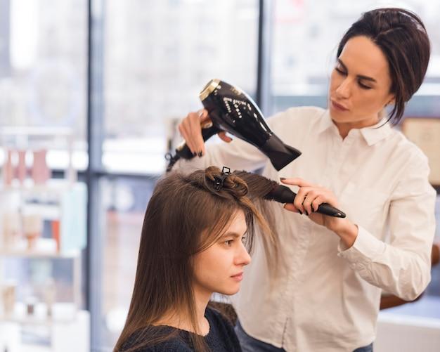 Femme brune se fait sécher les cheveux