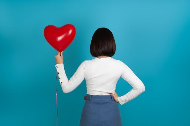 Femme brune se tient avec son dos et tient un ballon en forme de coeur rouge