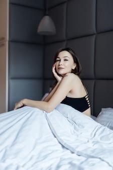 Femme brune sensuelle cheveux longs sur lit blanc dans une douce lumière du matin sous la couette