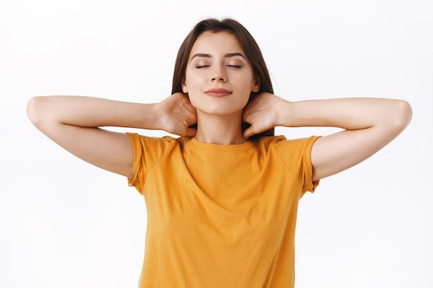 Femme brune sensuelle et séduisante, détendue et insouciante, se sentant soulagée et apaisée, les yeux fermés touchant son cou derrière et souriante ravie après les procédures de salon de spa, fond blanc