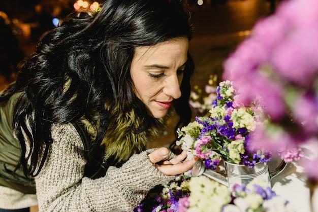 Femme brune sentant les fleurs sur un marché la nuit.