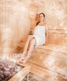 Femme brune en serviette relaxante au bain à la vapeur