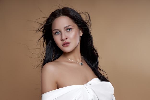 Femme brune sexy aux cheveux longs, corps mince de silhouette parfaite. maquillage naturel sur un visage de fille