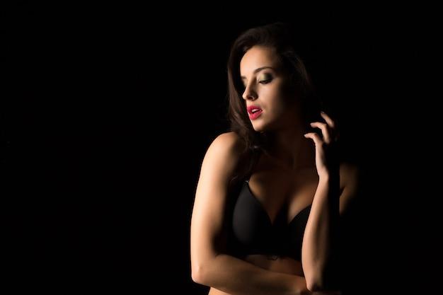 Femme brune sexy aux cheveux luxuriants en lingerie noire posant dans le noir. espace pour le texte